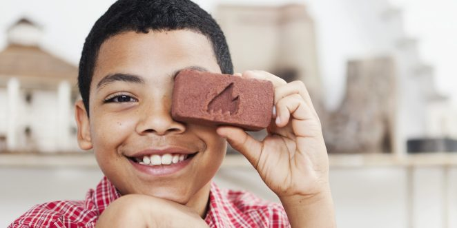 Smiling boy holding a miniature facing brick with Wienerberger logo in front of his left eye