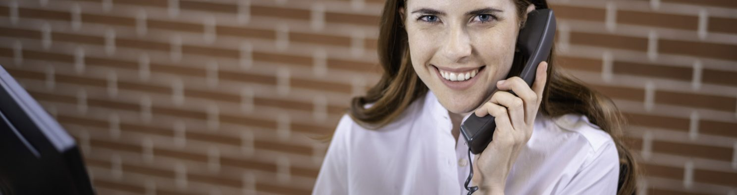 Smiling woman sitting next to computer screen holding a telephone receiver